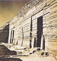 Πάνω από το έδαφος υψώνεται ένας απότομος βράχος με χαραγμένα αινιγματικά ιερογλυφικά.